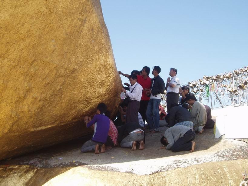 Chicos orando y pegando papeletas de oro a la roca dorada
