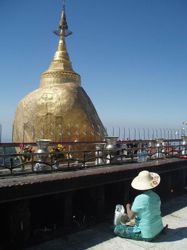 Mujer rezando frente a la roca dorada